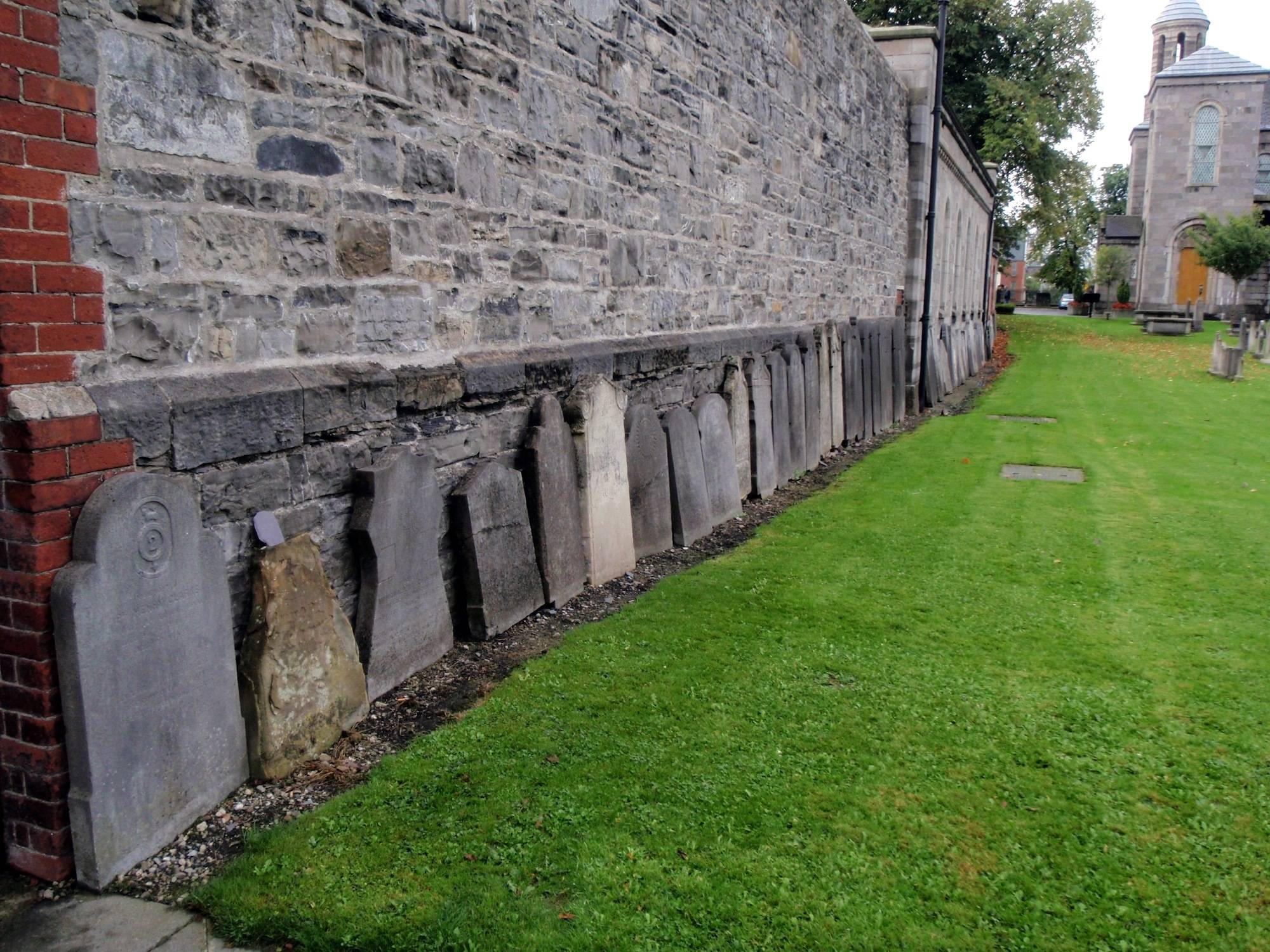 Older headstones leaning against the wall at Arbour Hill Cemetery. OPW.